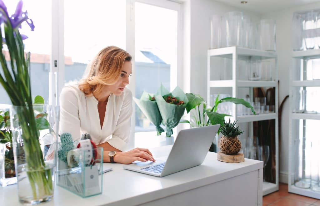 Small business owner using a laptop in a flower shop