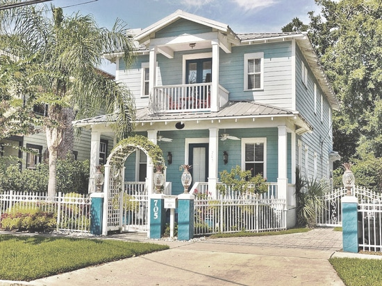 Two-story house (blue with white trim) with pineapple lights on top of each fence post.