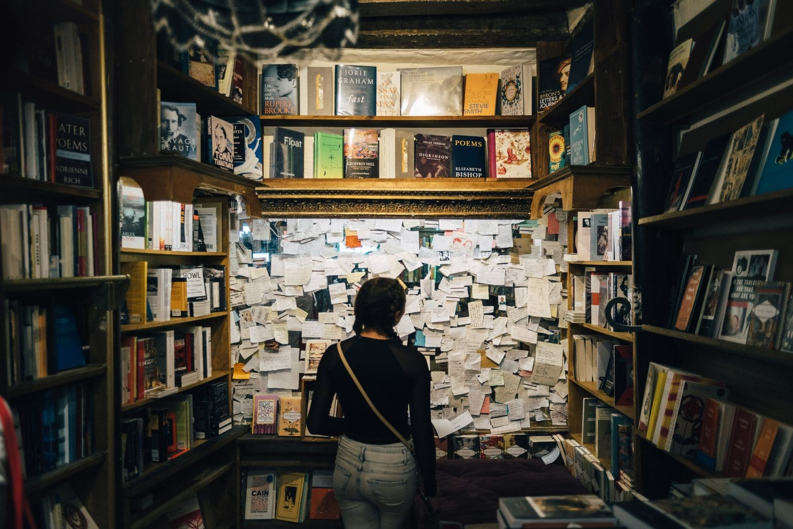 young woman looking at a cork board filled with hand-written notes and surrounded by shelves of books