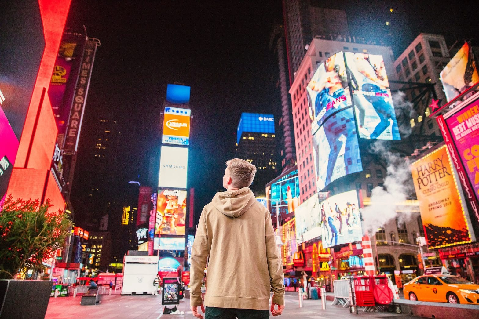Young man in a hoodie staring at digital advertisements in Times Square, New York City